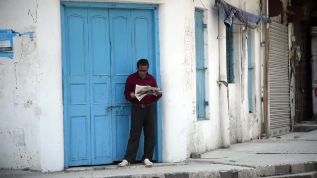 a man reading newspaper in a street in front of a closed shop - newspaper stock videos & royalty-free footage