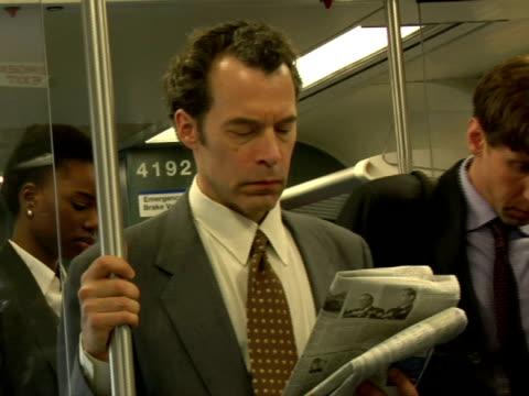 cu, man reading newspaper in subway train, chappaqua, new york state, usa - 薄毛点の映像素材/bロール