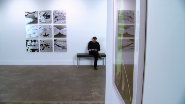 man reading newspaper on bench in gallery / marking paper with pen - kunstmuseum stock-videos und b-roll-filmmaterial