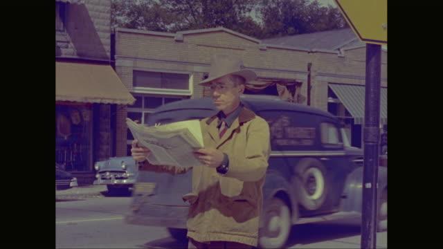 MS TU Man reading newspaper on roadside / United States
