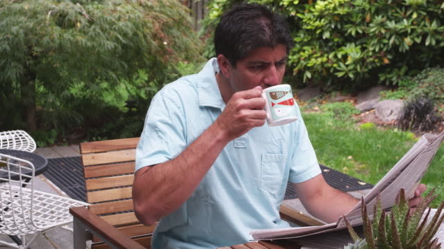 ms man reading newspaper outside on patio while drinking coffee / portland, oregon, united states - portland oregon homes stock videos & royalty-free footage