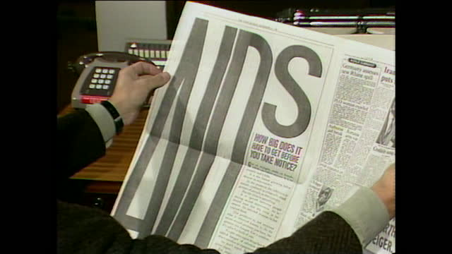 man reading newspaper revealing large aids awareness advert covering an entire page, uk; 1986. - advertisement stock videos & royalty-free footage