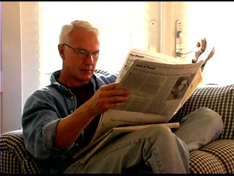 man reading newspaper - tre quarti video stock e b–roll