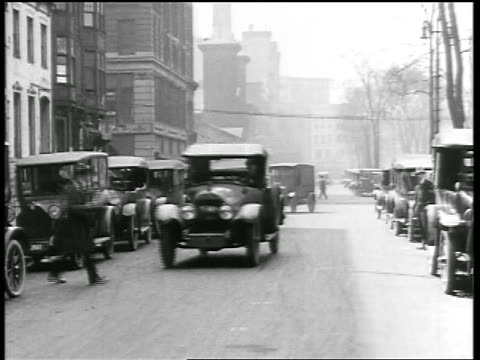 b/w 1919 man reading newspaper walking in front of car + almost gets hit / newsreel - newsreel stock videos and b-roll footage