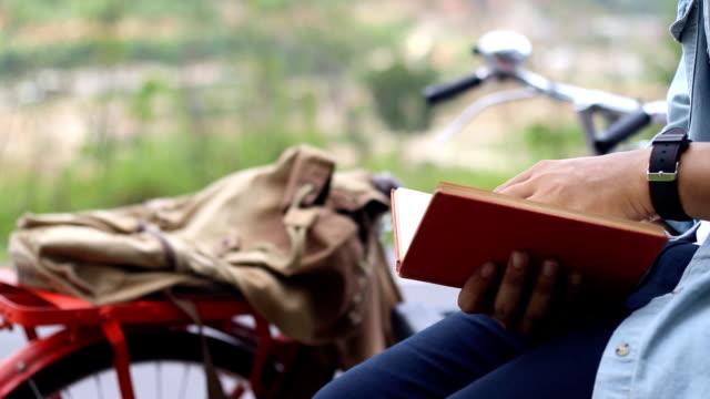 vídeos y material grabado en eventos de stock de hombre leyendo el viejo libro de viaje y planear el viaje en bicicleta vintage - old book