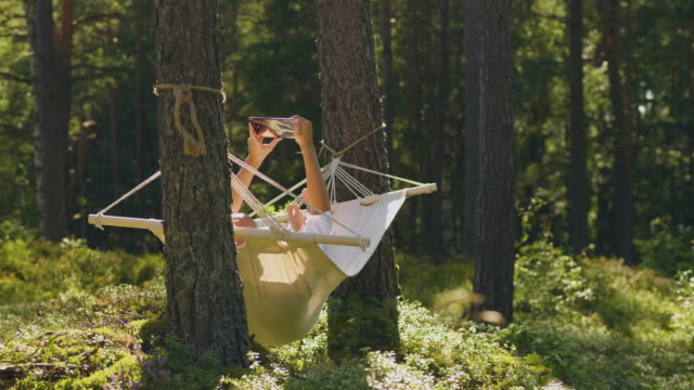 man reading on a tablet in a hammock - e reader stock videos & royalty-free footage