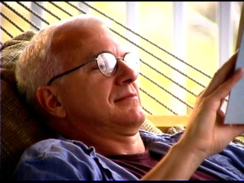 man reading on hammock - bald head island stock videos and b-roll footage