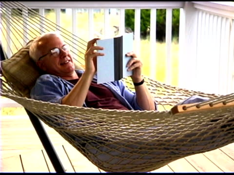 vídeos y material grabado en eventos de stock de man reading on hammock - only mature men