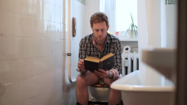 MS Man reading on toilet / Berlin, Germany