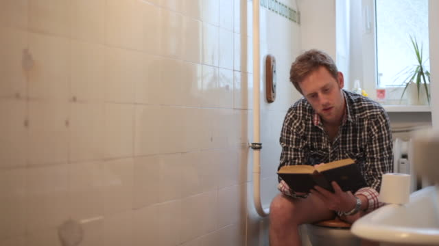 ms pan man reading on toilet / berlin, germany - toilet stock videos and b-roll footage