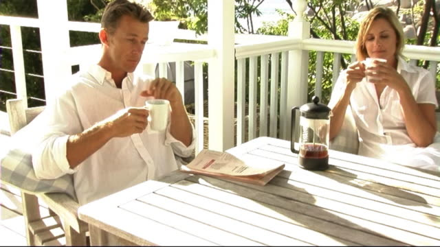 man reading paper on veranda - one mid adult man only stock videos & royalty-free footage