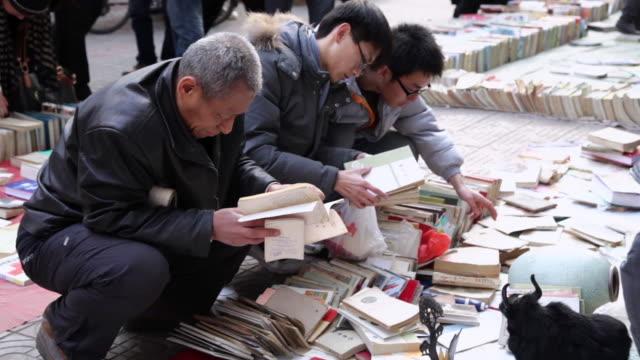 stockvideo's en b-roll-footage met ms man reading second hand book at market /xi'an, shaanxi, china - boekwinkel