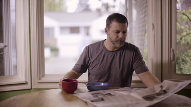 vídeos de stock e filmes b-roll de a man reading the newspaper, eating breakfast, and drinking coffee - jornal