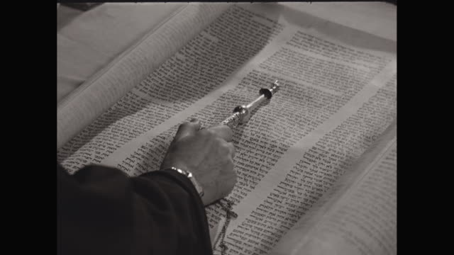 CU Man reading Torah scroll with pointer, or yad / United States