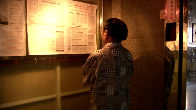 a man reads a notice board, china. available in hd. - vetrinetta video stock e b–roll