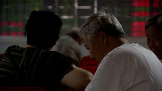 a man reads a paper near a flashing digital stock ticker, china. available in hd. - bbc news bildbanksvideor och videomaterial från bakom kulisserna