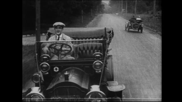 1915 a man reads directions while driving - フォード・t型モデル点の映像素材/bロール