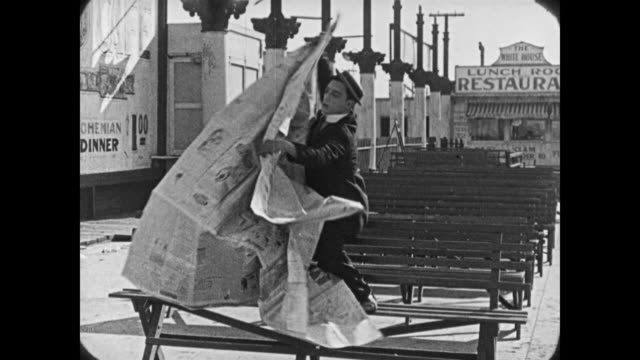 1921 man (buster keaton) reads giant newspaper at amusement park - buster keaton stock videos and b-roll footage