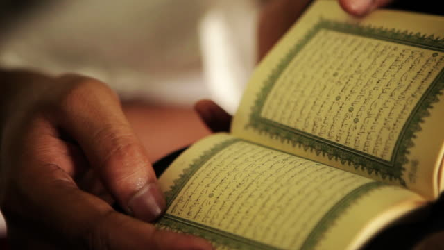 a man reads the quran. - koran stock videos and b-roll footage