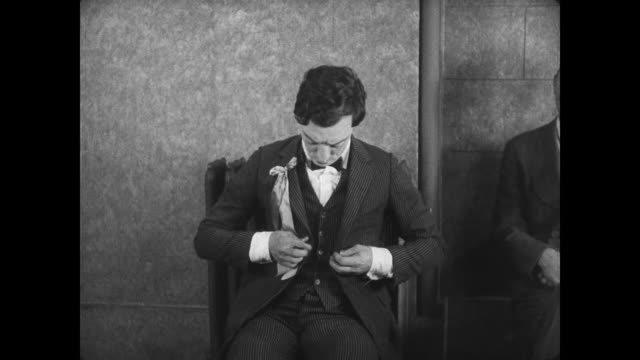 stockvideo's en b-roll-footage met 1927 man (buster keaton) realizes his suit has shrunk - nauw