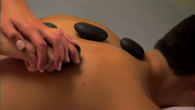 man receiving stone massage treatment - lastone therapy stock videos and b-roll footage