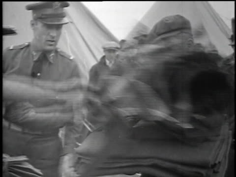 man receiving supplies and a uniform / man checking his supply kit / men having their feet measured - 1934 bildbanksvideor och videomaterial från bakom kulisserna