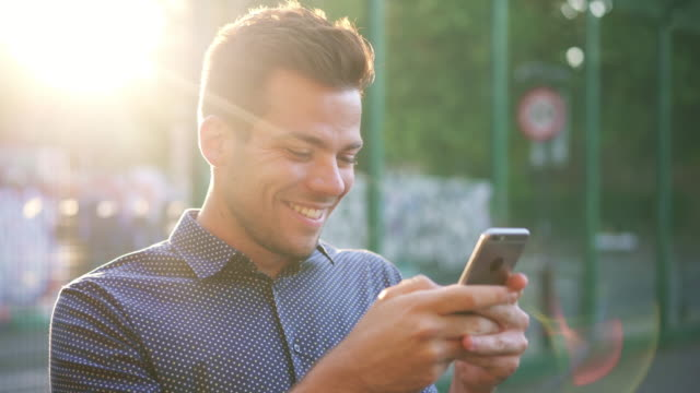 vidéos et rushes de man receiving text, smiling, replying, laughing with sun flare. real text conversation, sunset. - joie