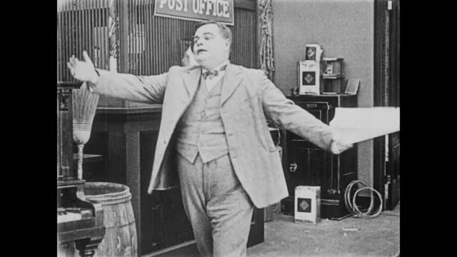 1919 man (fatty arbuckle) recites from newspaper and causes the audience to sob - fatty arbuckle stock videos and b-roll footage