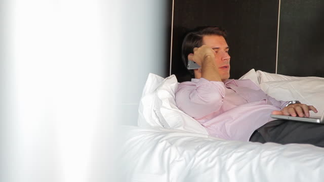 man reclining on bed using laptop, chatting on cell phone - zurücklehnen stock-videos und b-roll-filmmaterial