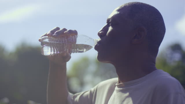 Man refreshes himself with a bottle of water.