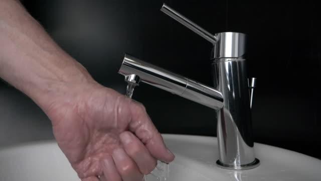 vidéos et rushes de homme rafraîchissant sa main dans l'évier de salle de bains - eau robinet