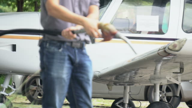Man refuelling a airplane at a petrol station