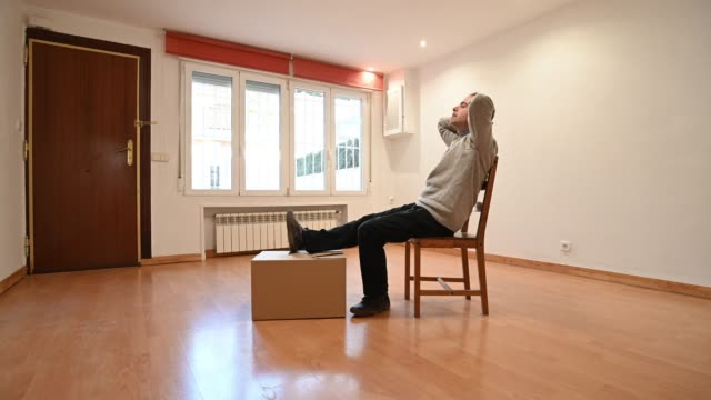vidéos et rushes de man relaxed wit his leg on a moving box - parquet