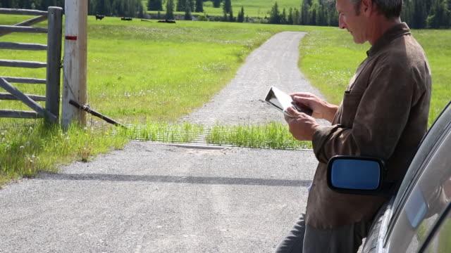 Man relaxes against car on rural road, uses digital tablet