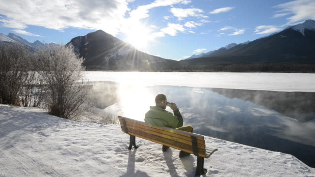 Man relaxes at lake bench, steam rising, sunrise