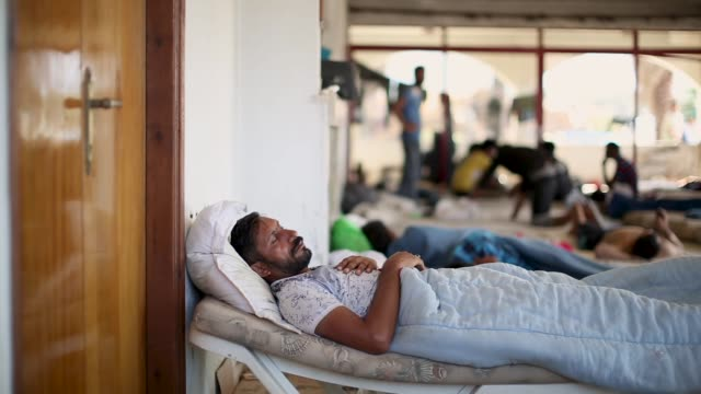 A man relaxes at sunset in an abandoned hotel that has given refuge to many migrant families on August 29 2015 in Kos Greece Migrants from many parts...