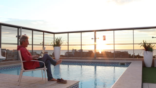 man relaxes by swimming pool, watches sunrise - person sitting cross legged stock videos & royalty-free footage