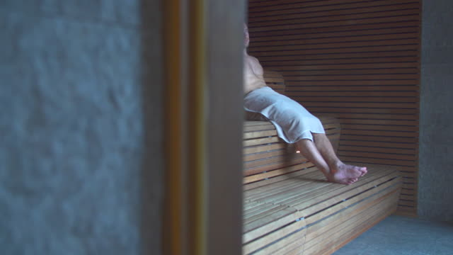 a man relaxes in a sauna at a luxury resort. - sauna stock videos & royalty-free footage