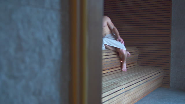 a man relaxes in a sauna at a luxury resort. - sauna stock videos and b-roll footage