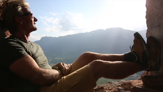 man relaxes in ancient window frame, looks out to mtns, sunrise - window frame stock videos and b-roll footage