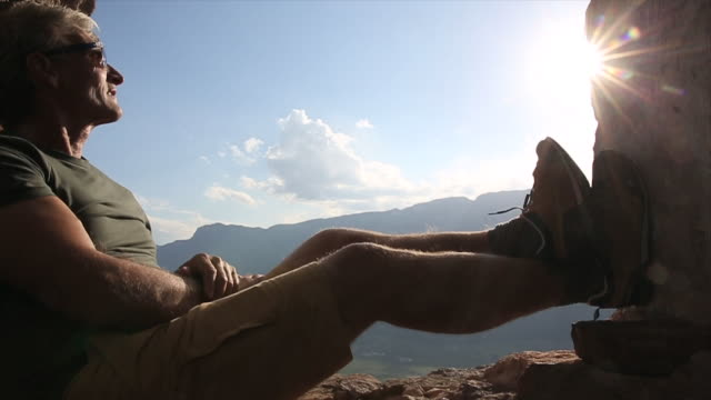 Man relaxes in ancient window frame, looks out to mtns, sunrise