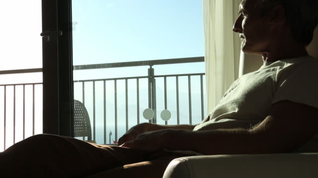 man relaxes in easy chair, uses digital tablet - armchair stock videos & royalty-free footage
