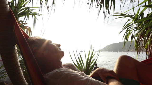 man relaxes in hammock, palm fronds and sea behind - hammock stock videos & royalty-free footage