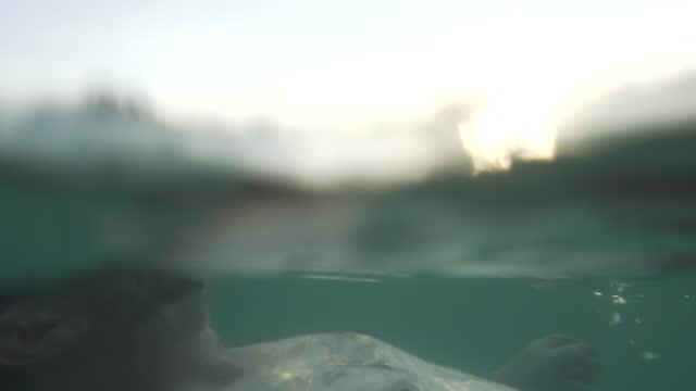 vídeos y material grabado en eventos de stock de hombre se relaja en el mar al atardecer - surface level