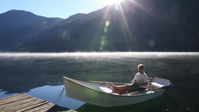 Man relaxes in rowboat on mtn lake, uses digital tablet