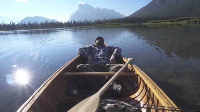 man relaxes in wooden canoe, mountain lake - liegen stock-videos und b-roll-filmmaterial