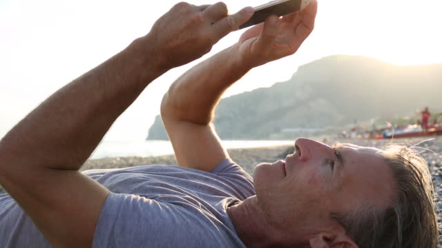 Man relaxes on beach, sending text on smart phone