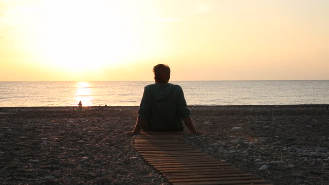Man relaxes on beach walkway, watches sunrise over sea