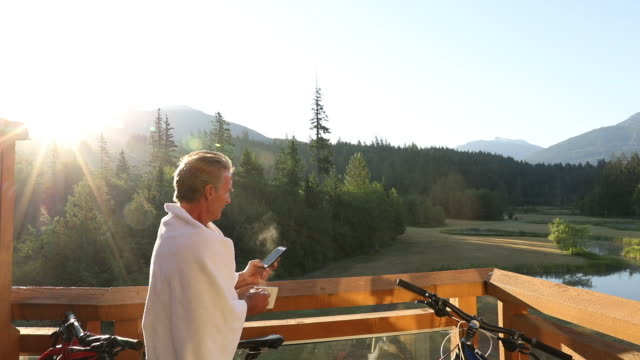 Man relaxes on deck at sunrise, looks out to mountain scene