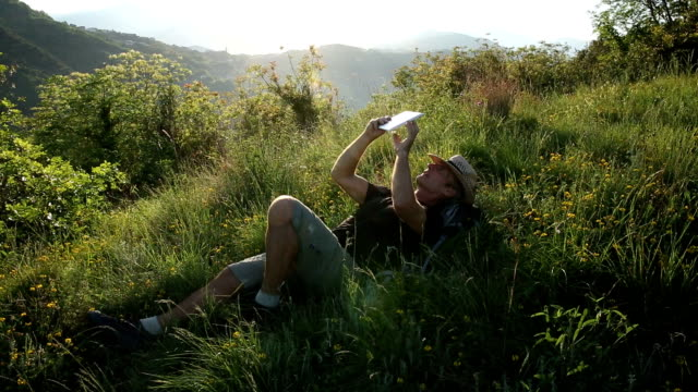 man relaxes on grassy hillcrest at sunrise, uses digital tablet - rucksack stock videos & royalty-free footage